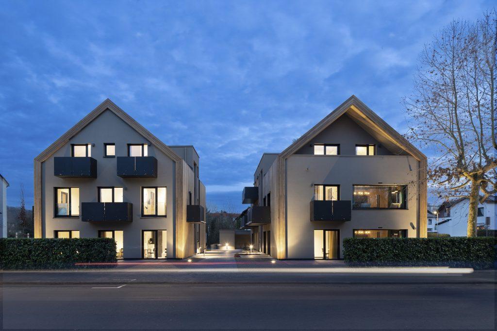 Zwei neugebaute Häuser aus Holz in der Abenddämmerung.